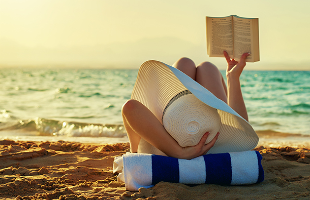 Woman reading a book while laying on the beach.