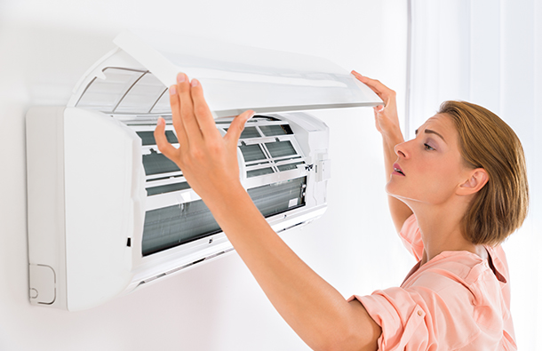 Woman checking air conditioning unit