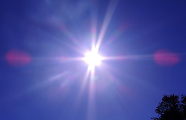 Blue sky with sun and sun flare on camera lens