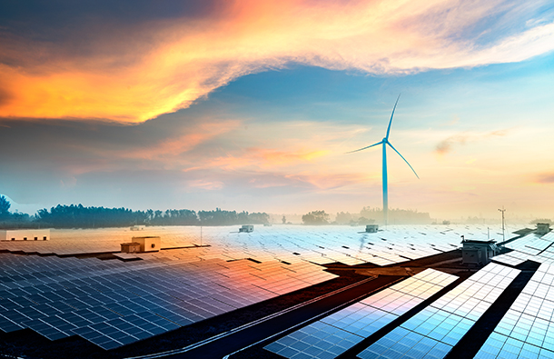 Solar panels and a wind turbine together at sunrise
