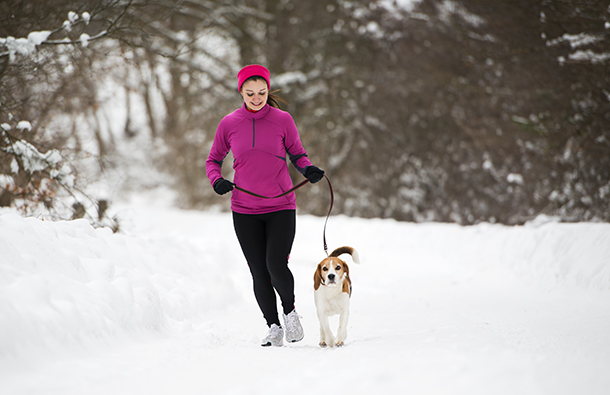 Woman walking her dog in winter weather