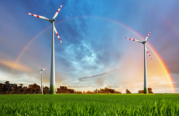 Wind turbines in a green field with dramatic sky and rainbow