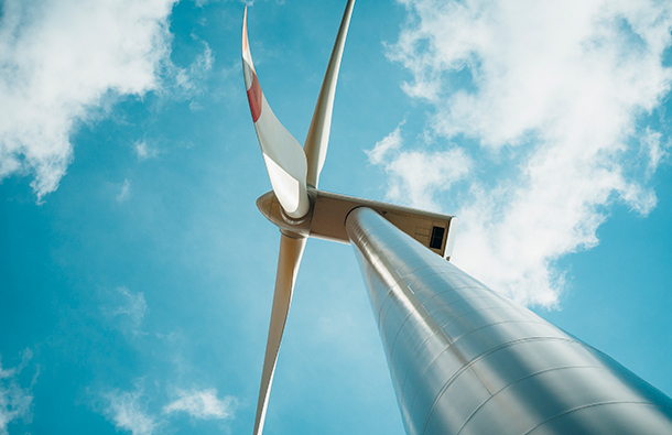 Low angle view of wind turbines with blue sky and clouds