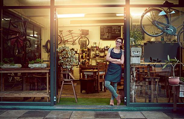 Small business female shop owner smiling on her storefront's doorstep