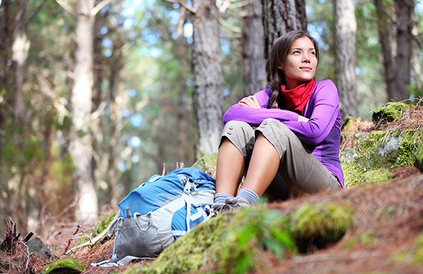 young Asian women hiker who's sitting in the forest on a break