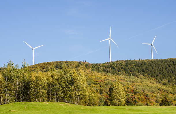 Wind turbines along a hillside with lots of green brush and trees