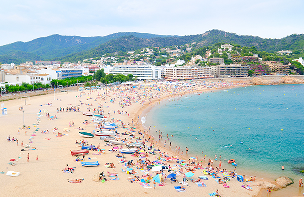 Aerial view of a European beach and hotels scene with mountains in the background