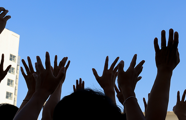 Silhouette of crowd's hands upraised at an outdoor event