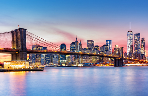 Dusk view of New York City skyline across the Hudson River with Brooklyn Bridge