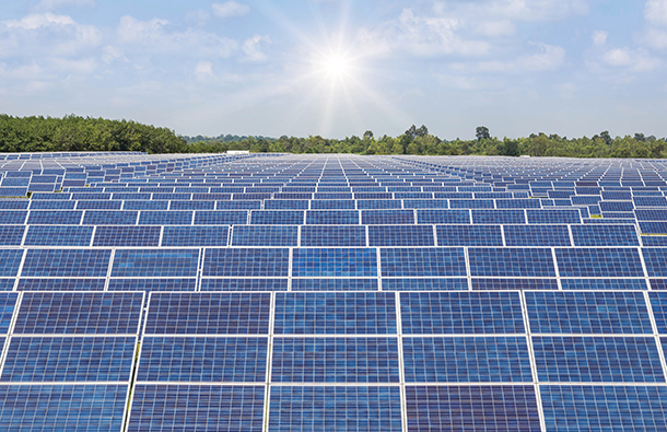 Solar panel array in a rural setting with sun shining