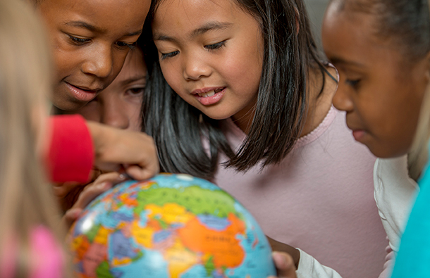 Diverse group of kids looking at a globe together in a classroom environment