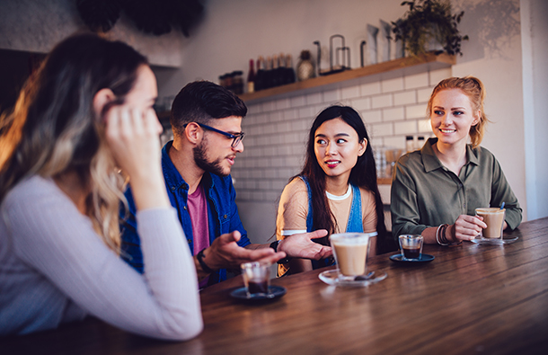 Group of young people talking together at a coffee house