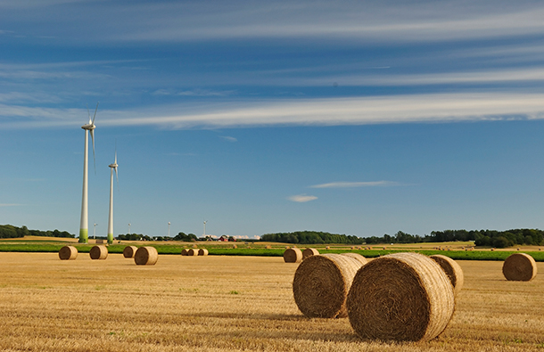 Wind turbines on farmland with hay bales in the foreground