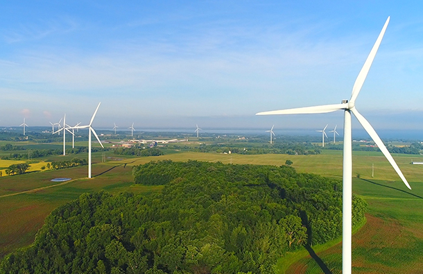Aerial view of green landscape with wind turbines on it.