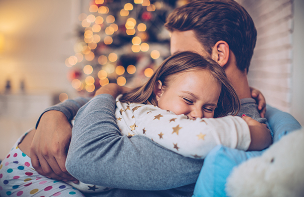 Closeup image of a little girl hugging her father in front of sparkling holiday lights