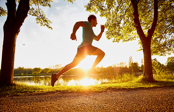 A fast running man with sunlight behind him