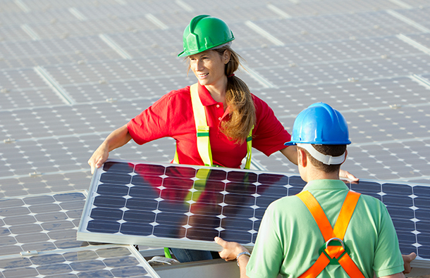 Young woman and young man solar technicians installing solar panels.