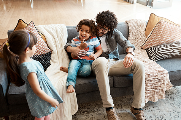 Father and two kids hanging out on couch together