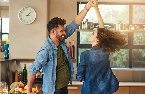 Young couple dancing in their brightly lit kitchen