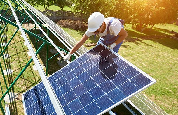 Solar technician installing solar panels for a solar installation site