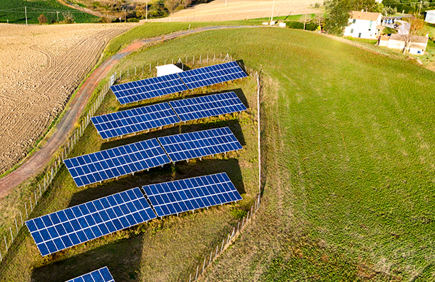 Aerial view looking over a small, rural solar farm near houses.