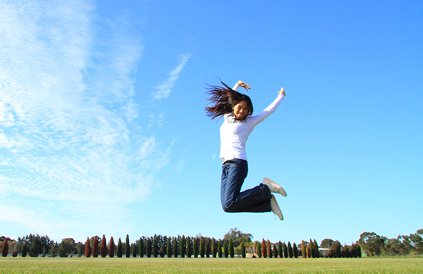 Young Asian woman jumping for joy in green park