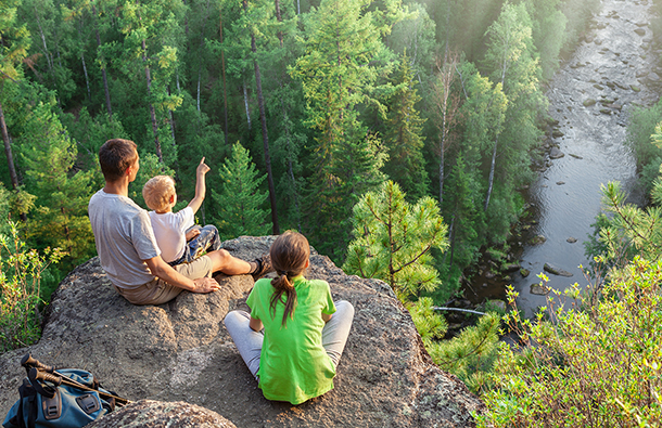 Young couple and child sitting on rocky overlook admiring a beautiful forest