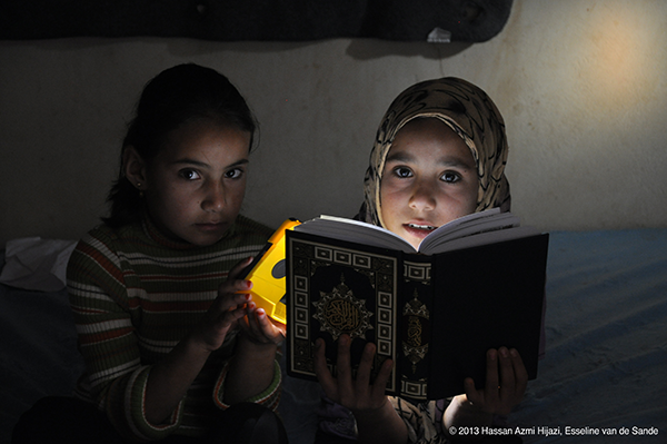 Two young girls reading a book with the help of a solar powered flashlight.