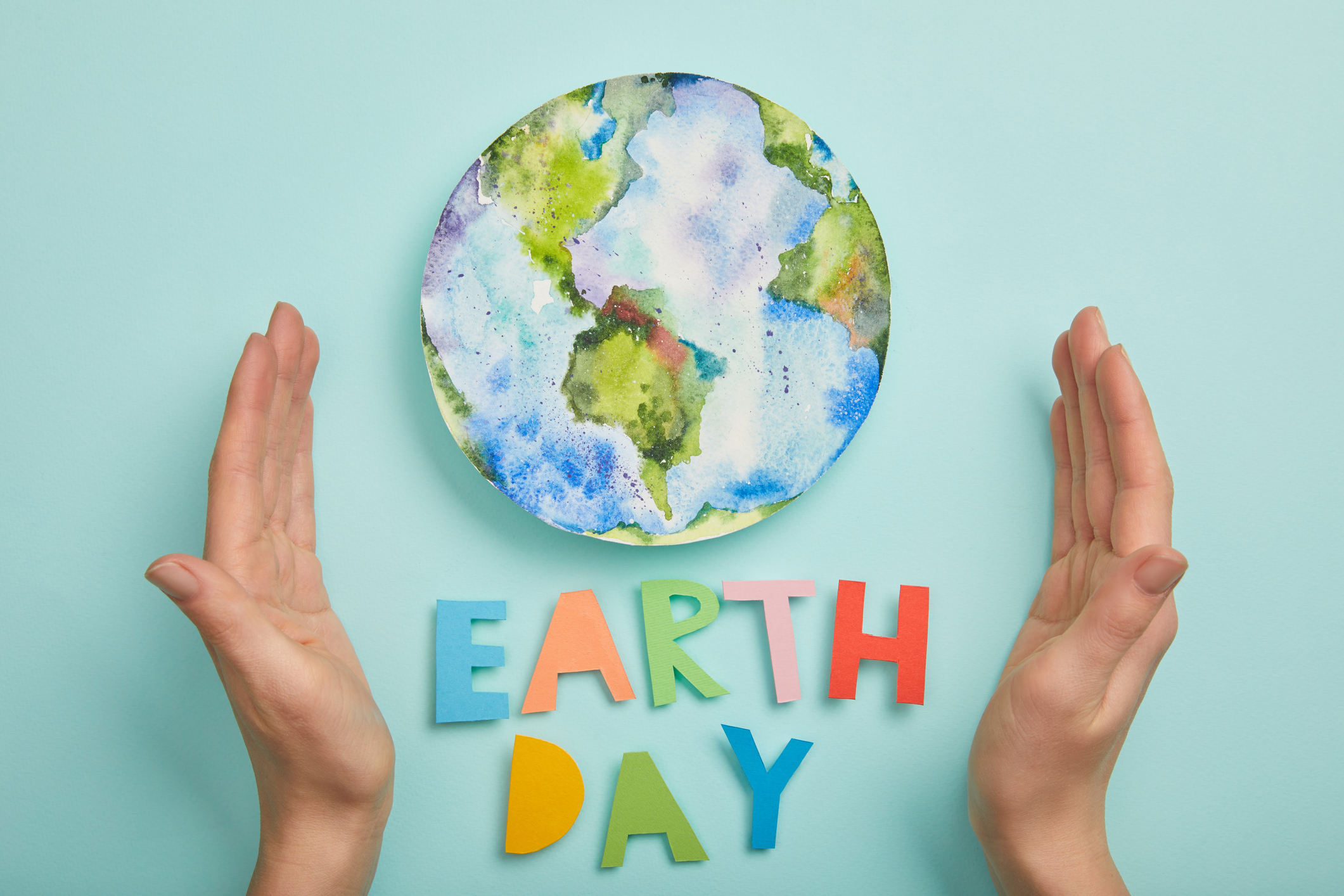 """A water color painting of the earth, with colorful letters spelling """"Earth Day"""""""