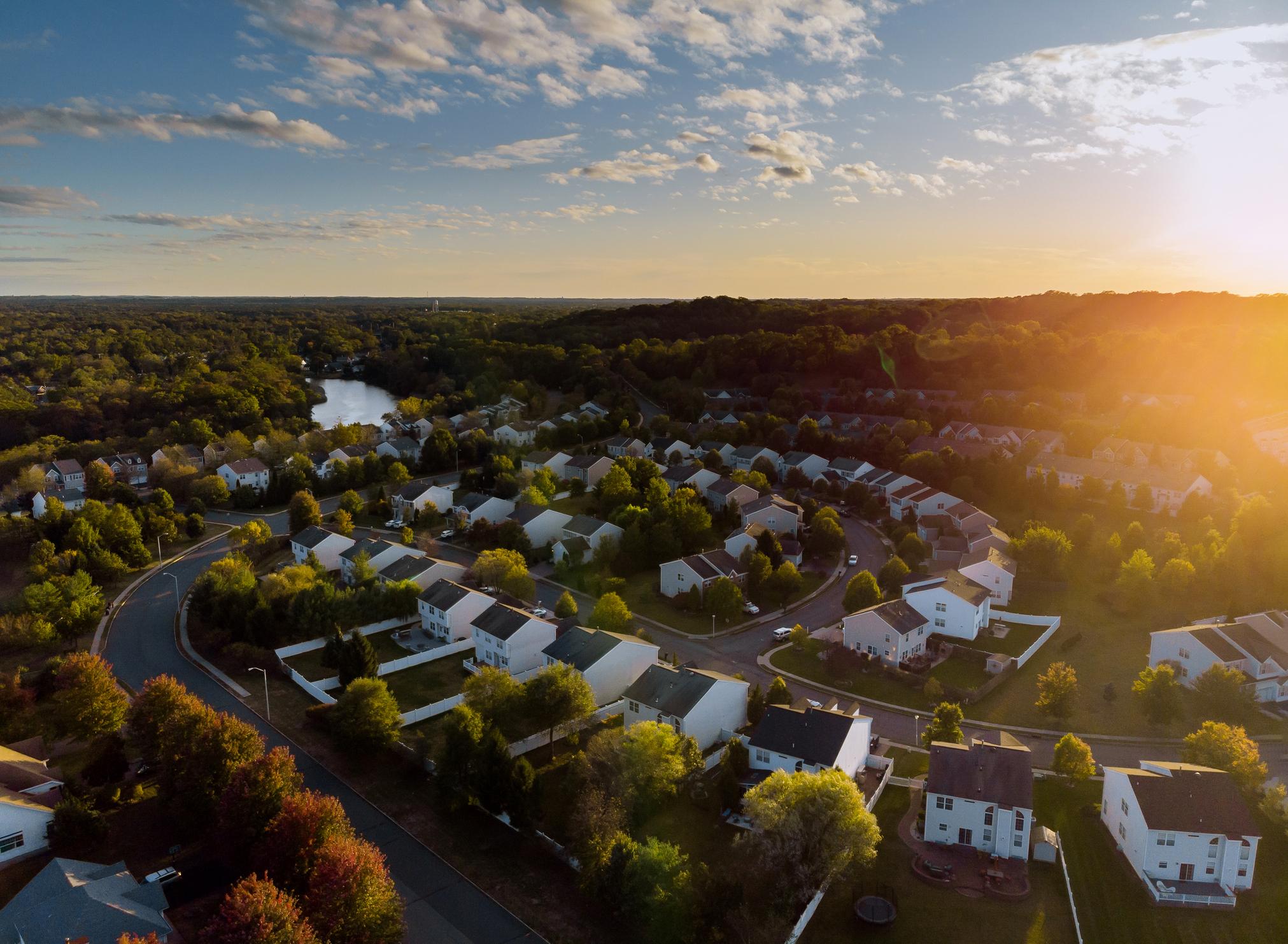 Sun rising over a suburban neighborhood with lush green trees.