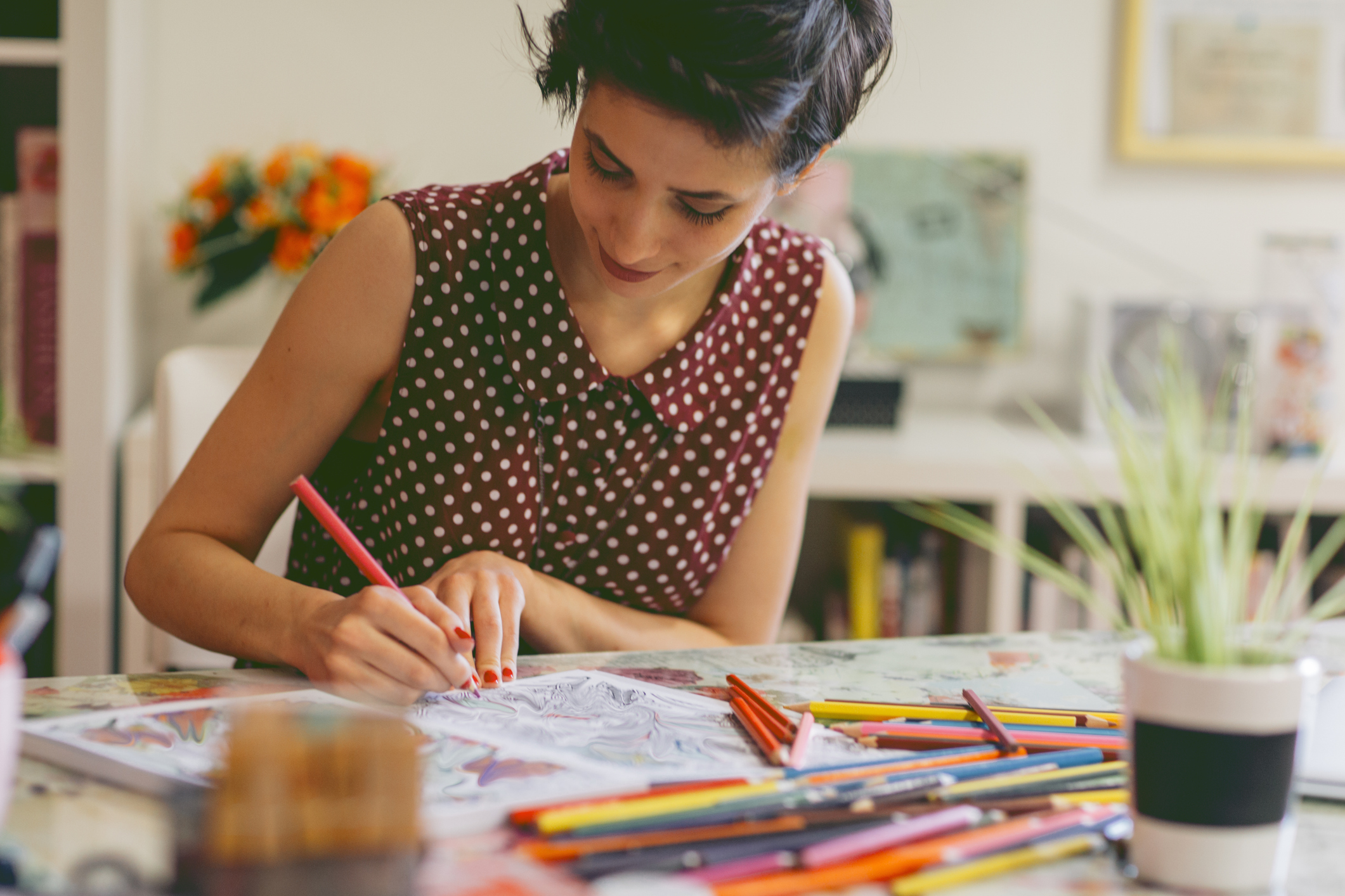 Woman adult coloring while social distancing inside her home.