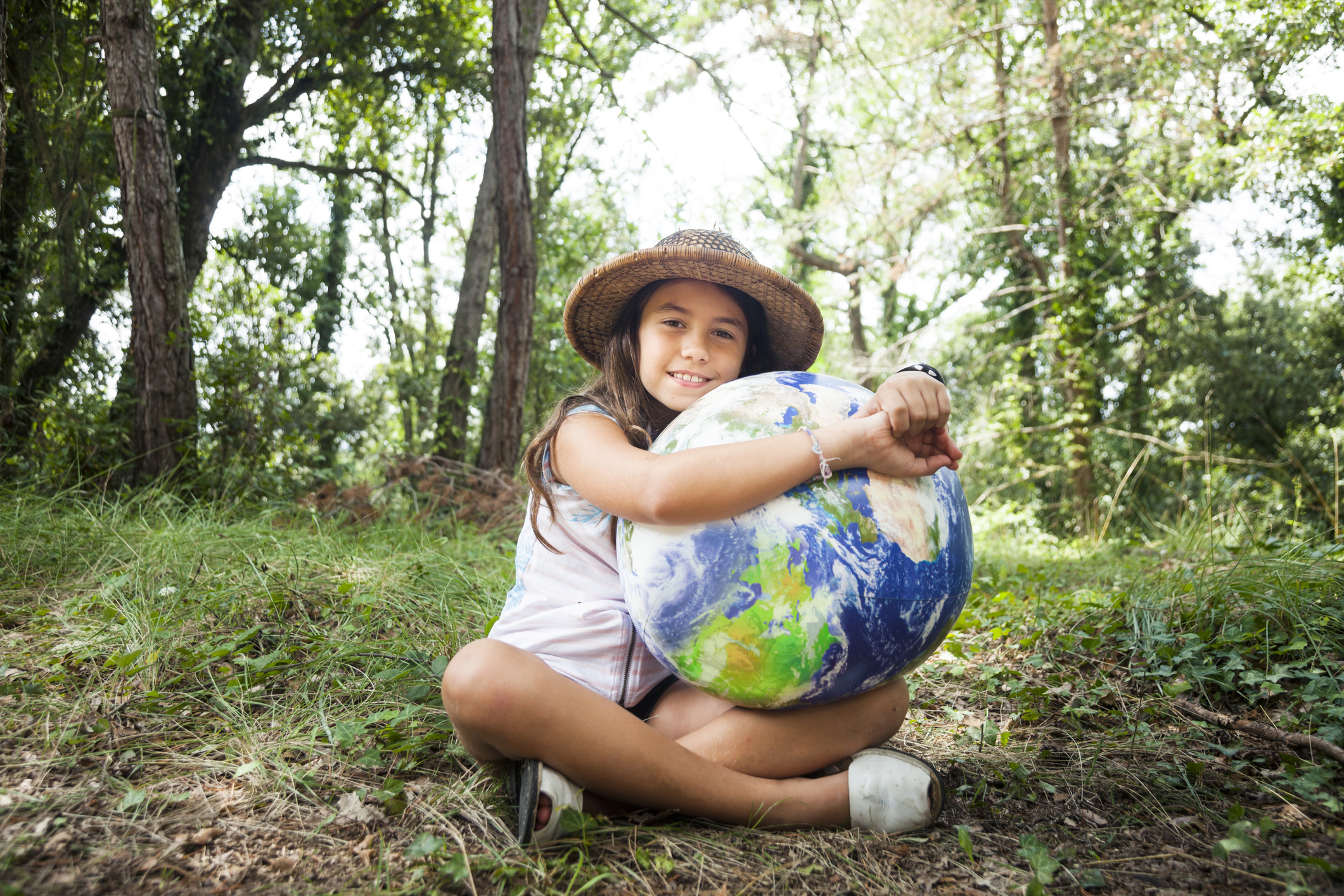 Young girl sitting in a forest hugging a globe.